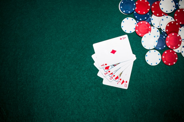 Royal flush playing card and casino chips on green poker background Free Photo