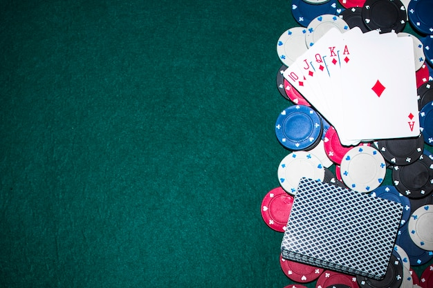 Royal flush playing card over the casino chips on green poker table Free Photo