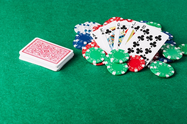 Royal flush playing card and casino chips on green poker table Free Photo