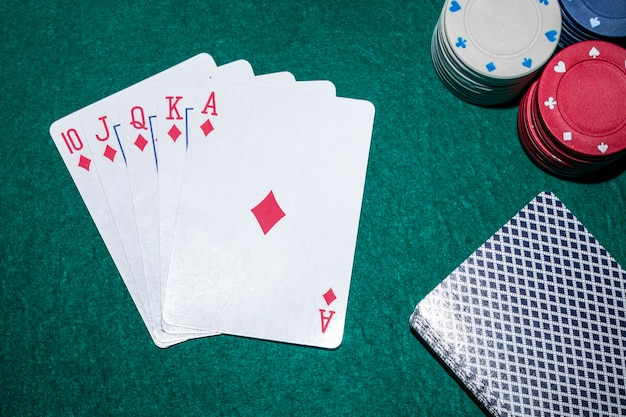 Royal flush playing cards with casino chips on poker table Free Photo