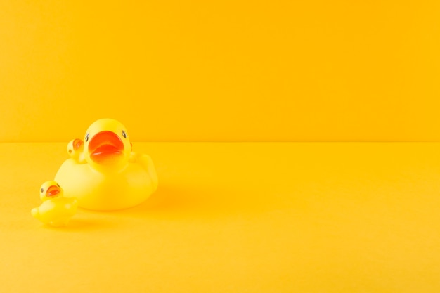 Rubber duck and ducklings on yellow backdrop Free Photo
