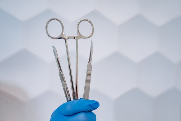 A rubber gloved hand holds two scalpels and a clamp Free Photo