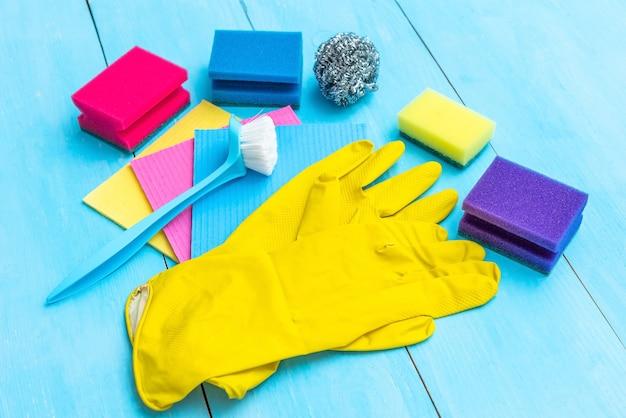 Резиновые перчатки, щетка и тряпки на синем фоне. Premium Фотографии