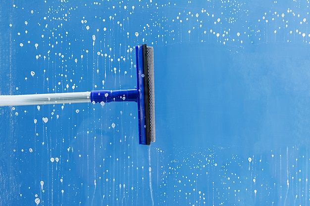Rubber squeegee cleans window. clears a stripe of soaped window. cleaning service concept. Premium Photo