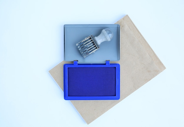 Rubber stamp and blue ink cartridges on brown book against white background. Premium Photo