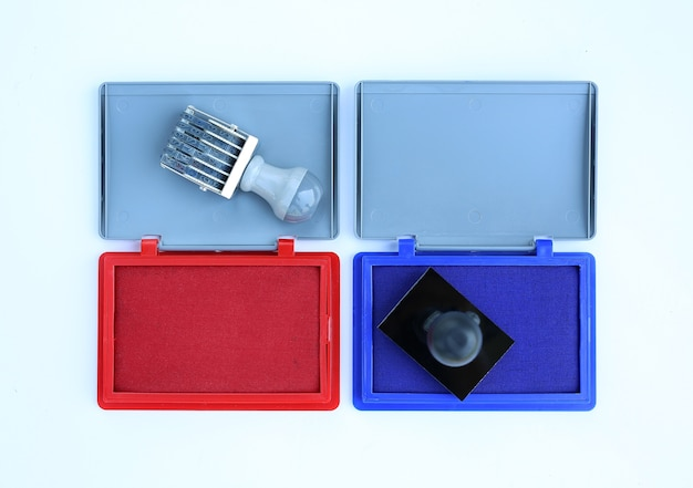 Rubber stamp and red - blue ink cartridges on white background. Premium Photo