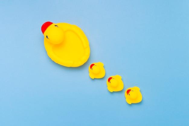 Резиновая игрушка желтого цвета мама-утка и маленькие утята на синем фоне. понятие материнской заботы и любви к детям, воспитания и образования детей. плоская планировка, вид сверху Premium Фотографии