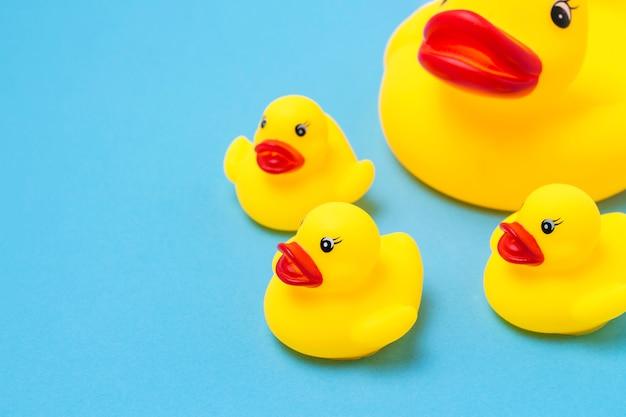 Резиновая игрушка желтого цвета мама-утка и маленькие утята на синем фоне. концепция материнской заботы и любви к детям, воспитание и образование детей Premium Фотографии