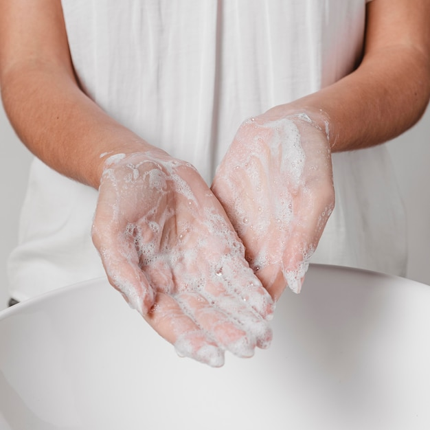 Rubbing hands with water and soap front view Free Photo