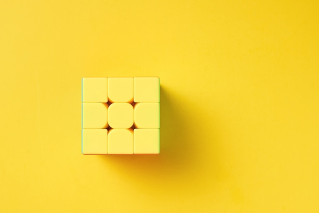 Rubics cube on a yellow background, top view Premium Photo