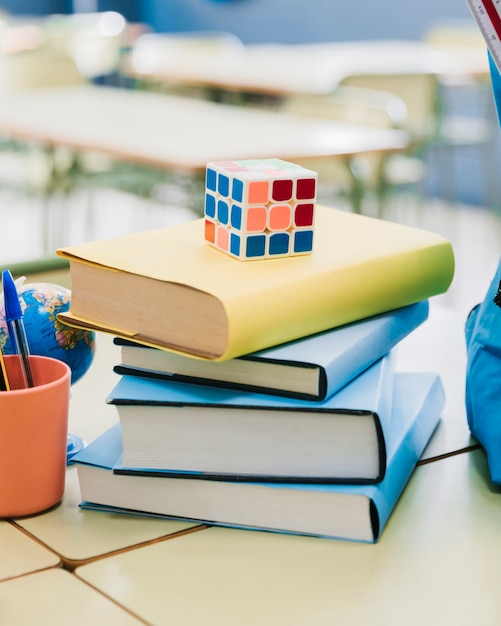 Rubik cube placed on stacked books on desk in classroom Free Photo