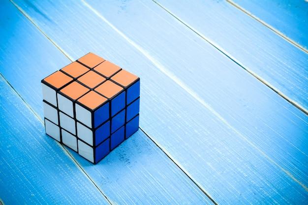 Rubiks Cube On Blue Wooden Desk Background Photo Premium Download