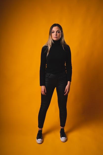 Рыжеволосая девушка с черными поднятыми волосами стоит посреди желтой комнаты в черной рубашке и брюках Premium Фотографии