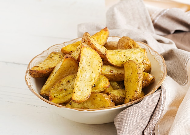 Ruddy baked potato wedges with garlic on a white background. Premium Photo