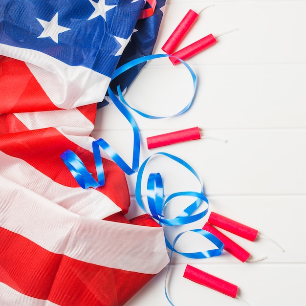 Ruffled american flag; blue ribbon and dynamite firecrackers on wooden table Free Photo