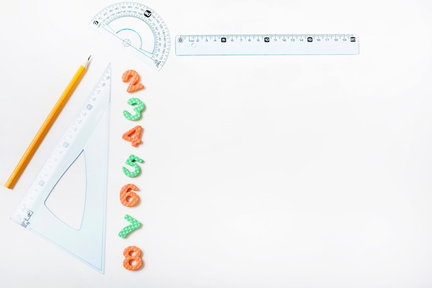 Rulers and pencil near figures Free Photo