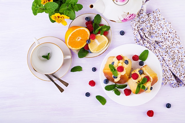 Rum baba decorated with whipped cream and fresh raspberry, blueberry. savarin with rum, cream and berries Premium Photo