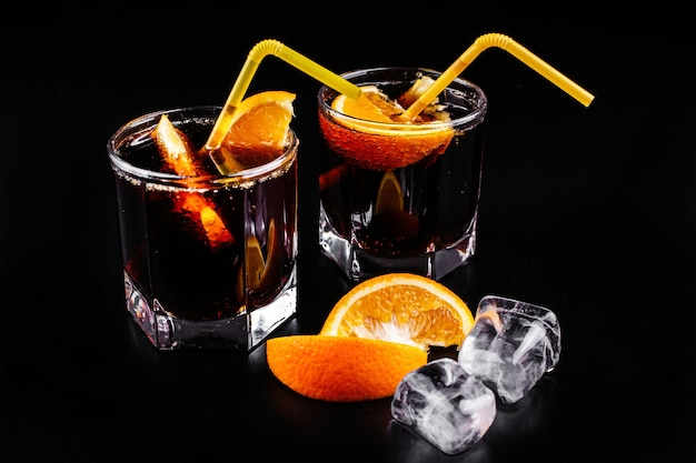 Rum and cola refreshing alcohol cocktail drink in highball glass with orange and ice Free Photo