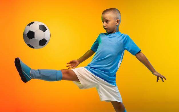 Запустить. молодой мальчик как футболист или футболист в спортивной одежде тренируется в градиентной желтой студии Бесплатные Фотографии