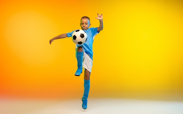 Run. young boy as a soccer or football player in sportwear practicing on gradient yellow studio Free Photo