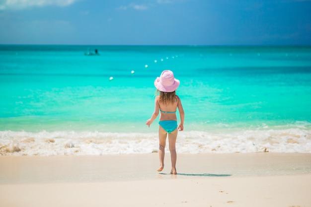 エキゾチックなビーチで浅い水の中のかわいい女の子runing Premium写真