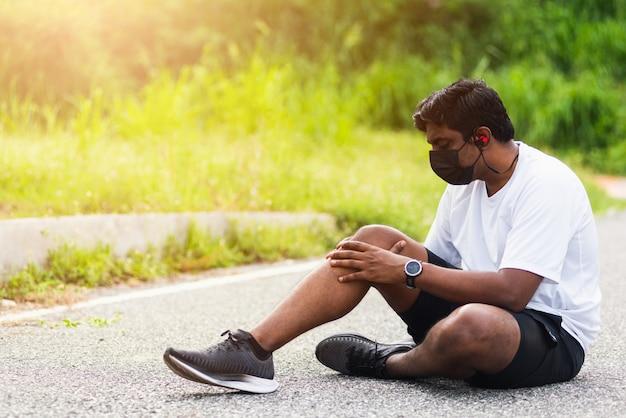 ランナーの黒人男性が座っている時計を着て、彼は走っている間彼の膝に手を関節保持します Premium写真