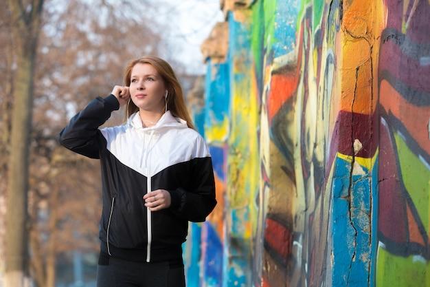 Runner girl putting on earphones Free Photo