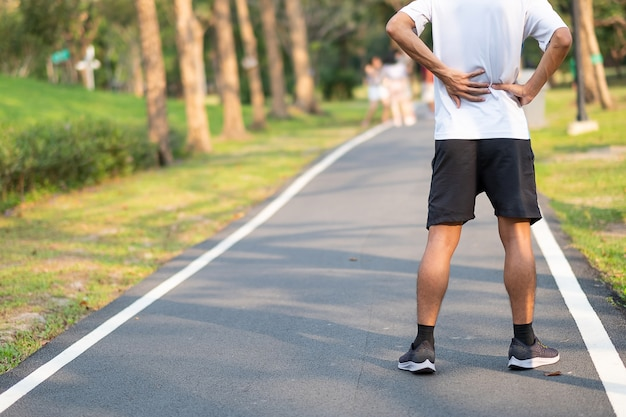 Runner having back ache and problem after running and exercise outside morning Premium Photo