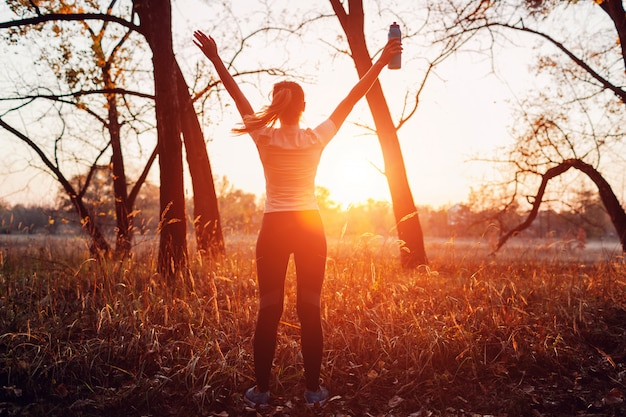 Runner raised arms after workout feeling free and happy succeeded in training, woman admiring sunset, Premium Photo