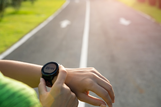 Runner setting up smart watch before training during sunset. exercise. Premium Photo