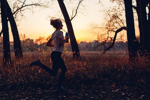 Runner training in autumn park. woman running with water bottle at sunset. active lifestyle. silhouette Premium Photo