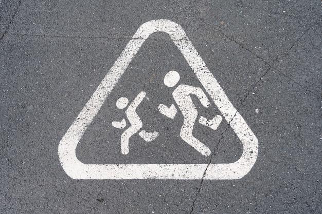 走っている子供、アスファルトに描かれた警告標識 Premium写真