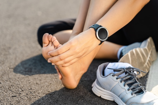 Running injury leg accident- sport woman runner hurting holding painful sprained ankle in pain. female athlete with joint or muscle soreness and problem feeling ache in her lower body. Premium Photo