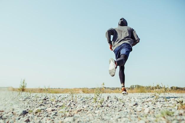 スポーツを実行しています。風光明媚な自然の中で屋外全力疾走の男性ランナー。マラソンランニングの筋肉男性アスリートトレーニングトレイルをフィットします。スプリントの圧縮服でワークアウトフィットのスポーティなアスレチック男 無料写真