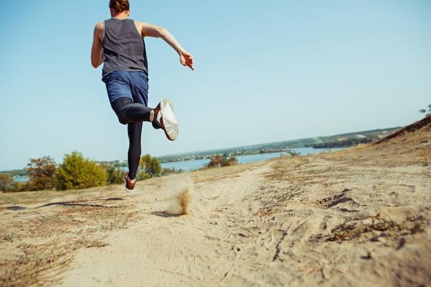 スポーツを実行しています。風光明媚な自然の中で屋外全力疾走の男性ランナー。マラソンランニングに適した筋肉質の男性アスリートトレーニングトレイルを装着します。 無料写真