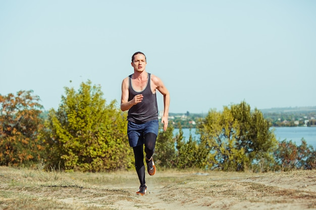 Running sport. man runner sprinting outdoor in scenic nature. fit muscular male athlete training trail running for marathon run. sporty fit athletic man working out in compression clothing in sprint Free Photo