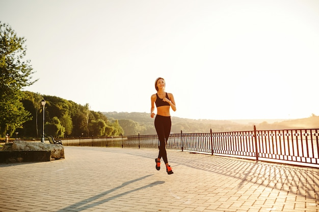 Running woman. runner jogging in sunny bright light. female fitness model training outside in park Free Photo