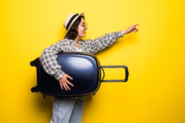 Бегущая женщина с чемоданом указал руками. красивая девушка в движении. путешественник с изолированным багажом. Бесплатные Фотографии