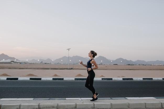 In esecuzione, allenamento su strada al mattino presto di gioiosa bella donna. formazione di forte sportiva, energia, motivazione, stile di vita sano, umore allegro. Foto Gratuite