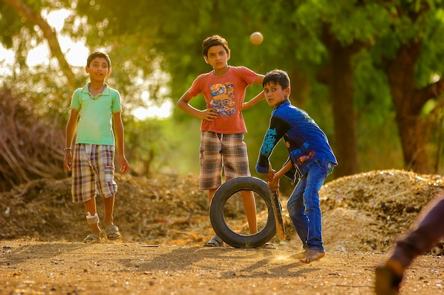 Rural indian child playing cricket on ground Premium Photo