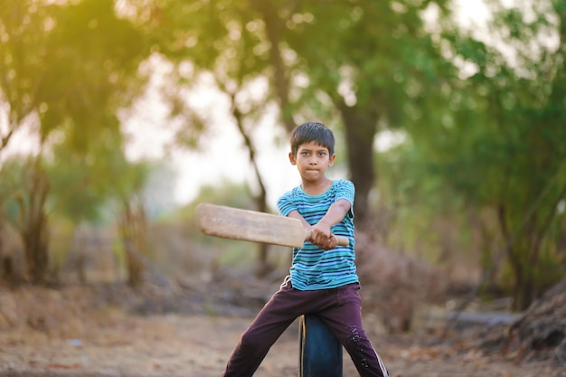 Rural indian child playing cricket Premium Photo