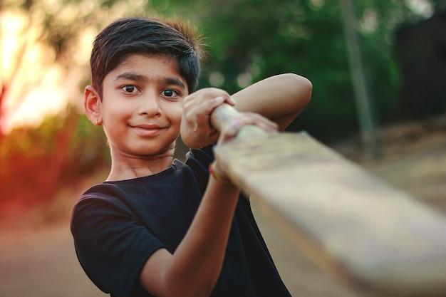 Rural indian child playing cricket Premium Photo