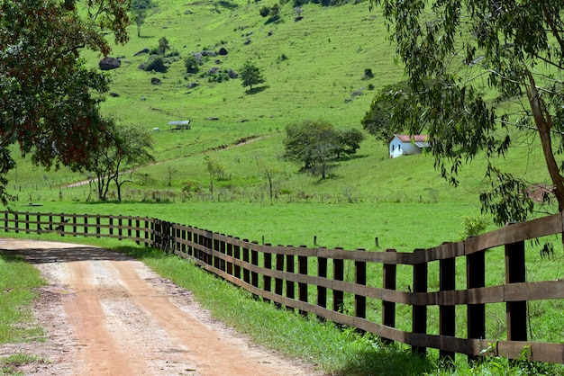 Rural landscape with foreground fence and small house in the background. minas gerai, brazil Premium Photo