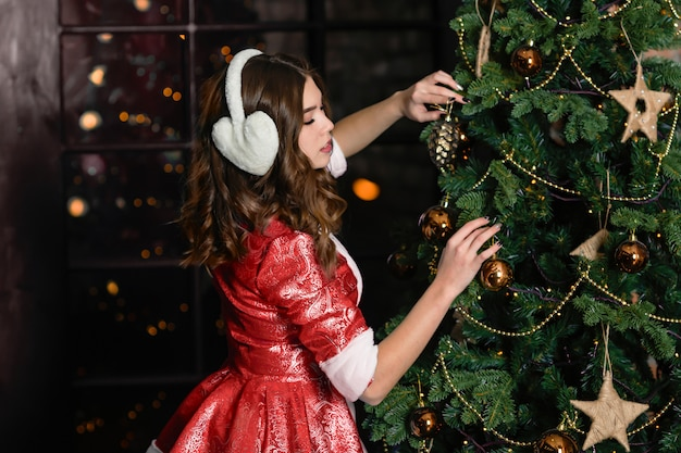 Russia, togliatti - november 13, 2018: christmas characters snow maiden. girl in a christmas costume decorates the christmas tree Premium Photo