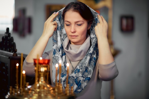 Russian beautiful caucasian woman with red hair and a scarf on her head is in the orthodox church Premium Photo