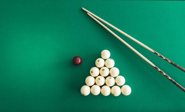Russian billiard balls, cue, triangle, chalk on a table. Premium Photo