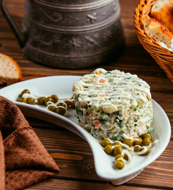 Russian capital salad with peas on the table Free Photo