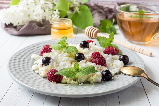 Russian cottage cheese with berries, honey mint, selective focus Premium Photo