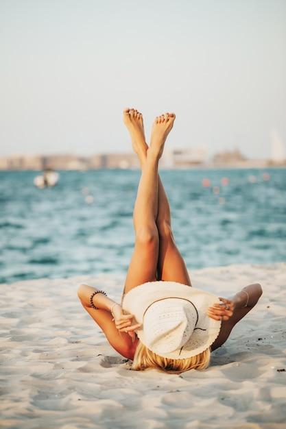 ビーチツアーを楽しんでいるアラブ海の青い海を見下ろす両足で白い砂の上に横たわる黒いビキニと帽子をかぶっているロシア人女性。写真はライフスタイル雑誌のコンセプトに最適です。 Premium写真