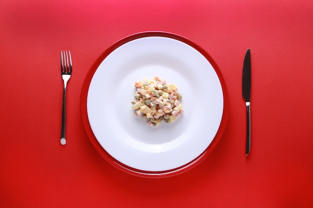 Russian new year or christmas salad on red background. Premium Photo